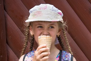 girl in a cap eats ice cream