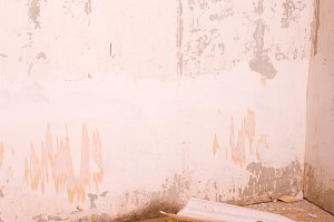 Dirty old room with torn wallpaper on the floor. Grunge vintage interior
