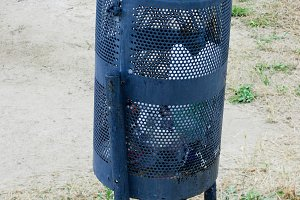 small black metal garbage container or urn on the street