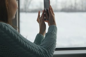 Young girl traveling in a train and using mobile phone to take a photo of the landscape outside the window. Beautiful woman takes pictures on a smartphone. Close up