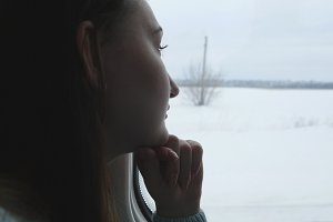 Young woman looking on window during riding on train. Profile of attractive girl traveling on railroad at winter time. Close up