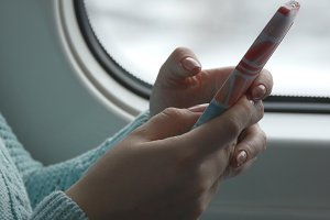 Young woman traveling in a train and using mobile phone. Female hand sends a message from the smartphone. Arm of girl chatting with friends. Close up