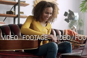 young latin smiling woman study online playing on acoustic guitar online using laptop computer