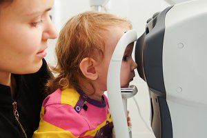 High tehnology in healthcare - optometrist in clinic checking little girl's vision - children's ophthalmology