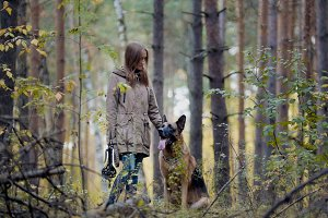 Young attractive girl and her pet - german shepherd - walking on a autumn forest