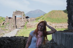 Beautiful red hair woman in glasses and shorts standing in pompeii, Italy - hot summer midday, horizontal