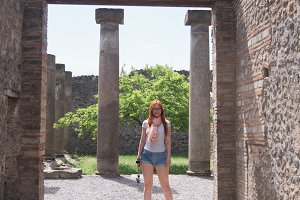 Attractive red hair woman in glasses and shorts standing in pompeii, Italy - hot summer midday