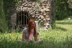 Red hair woman in green grass in pompeii, Italy - hot summer midday