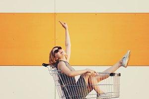 beautiful blonde girl sitting in shopping basket