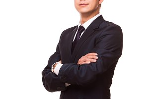 Young handsome businessman in black suit is standing straight with crossed arms, full length portrait isolated on white background