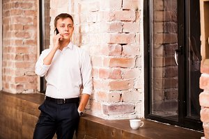 Handsome businessman in white shirt is speaking on the phone near the brick wall. There is a cup of coffee nearby