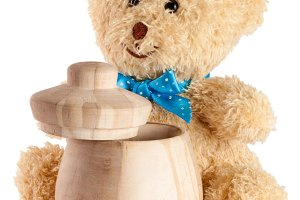 Toy teddy bear with wooden barrel isolated on white background