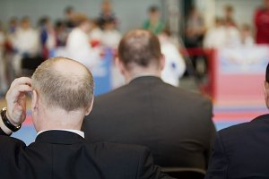 Martial art competitions - three bald men coaches looking at karate kid's fighting