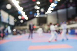 Female karatekas fight on karate competitions, de-focused sport background