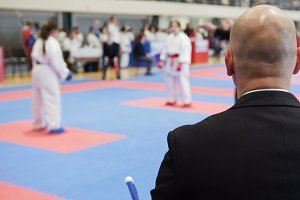 Martial art competitions - bald man coach-judge looking at karate teenager's fighting