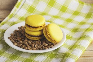 Yellow macaroons on a plate with green coffee