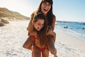 Smiling woman giving piggy back