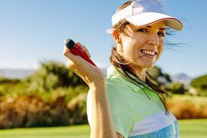 Happy female golfer with golf club
