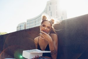 Portrait of funny beautiful girl eating donut