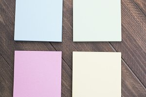 Multicolored paper notes on brown wooden background.