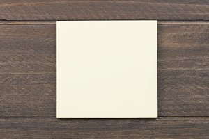 Yellow paper note on brown wooden background.