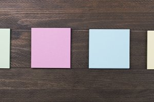 Multicolored paper notes on brown wooden background. Horizontal shoot.