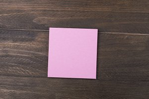 Pink paper note on wooden background.