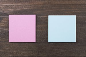Pink and blue paper note on wooden background.