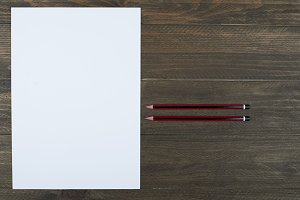 Blank sheet next to pencils on brown wooden table.