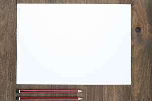 Blank sheet next to pencils on brown wooden table. Horizontal shoot.