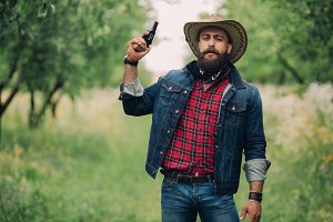 Bearded cowboy with gun.