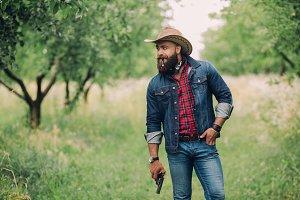 Bearded cowboy with gun.