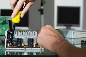 Computer engineer repairing hardware with screw driver