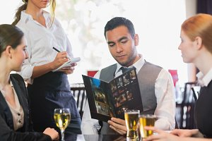 Handsome businessman ordering dinner from waitress