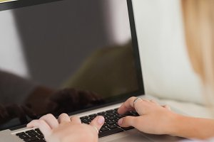 Blonde woman typing on laptop
