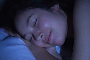 Young asian woman sleeping happily at night