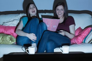 Two laughing friends on the couch watching tv together in the dark