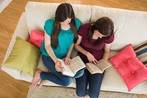 Two friends reading books on the couch