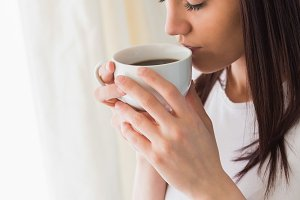Thoughtful girl holding a cup of coffee eyes closed