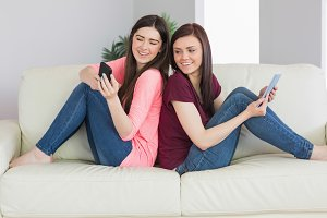 Two smiling girls sitting on sofa using tablet pc and mobile phone