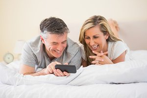 Happy couple lying on bed and watching a mobile phone