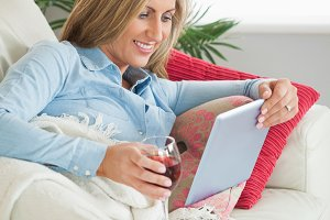 Smiling woman lying on a sofa drinking wine and using a tablet pc