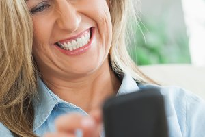 Happy woman typing on her mobile phone