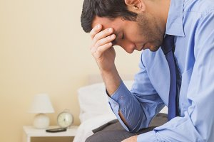 Upset man sitting head in hands on his bed