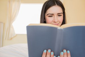 Relaxed girl lying on a bed reading a book