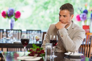 Handsome man waiting for his girlfriend at restaurant