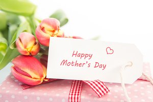 Bouquet of tulips next to a gift with a happy mothers day card