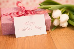 Pink wrapped present with bunch of white tulips and mothers day card