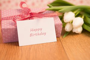 Pink wrapped present with bunch of white tulips and happy birthday card