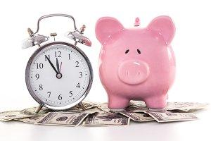 Pink piggy bank beside alarm clock on dollars